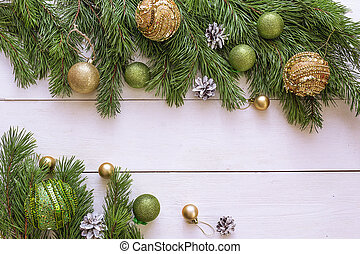 Christmas background with border of fir branches and decorations on white wooden table. Space for text or design.