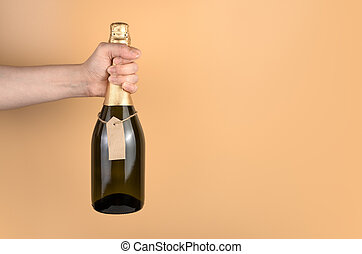 Christmas background with champagne in the hand of a woman on an orange background.