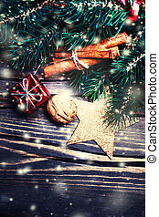 Christmas background with decorations, fir tree branch and gift boxes on wooden board with snowflakes
