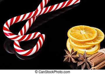 Christmas background with dried slice of orange, cinnamon stick and candy cane