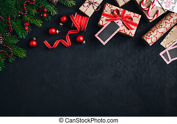 Christmas background with fir branches and cones gift boxes with red bow ribbon on a dark concrete background.