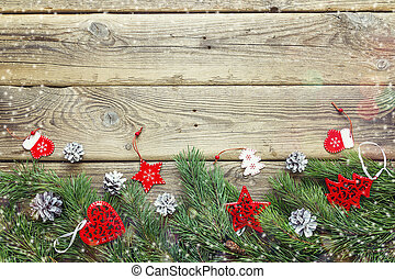 Christmas background with fir branches and decorations on old wooden table. Space for text or design.