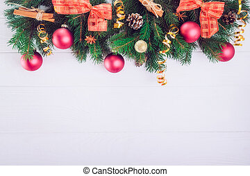 Christmas background with fir branches, new year decor, toys and spices on the white wooden backdrop. Top view with copy space. Selective focus,