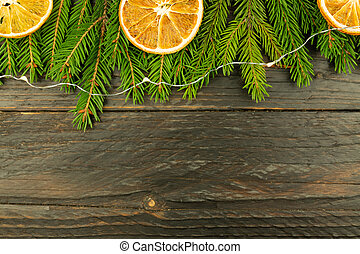 Christmas background with fur-tree branches, dried oranges on wooden background.