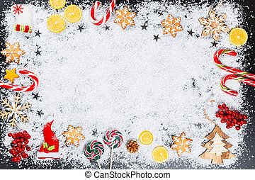 Christmas background with gingerbread snowflakes, white snow, toys, lemon, candy and New Year decor. Winter Holiday frame on a black wooden table