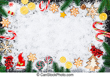 Christmas background with gingerbread snowflakes, white snow, toys, lemon, candy, Christmas tree branches and New Year decor. Winter Holiday frame