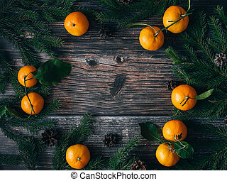 Christmas background with Mandarins, fir branches and pine cones. Winter holiday frame
