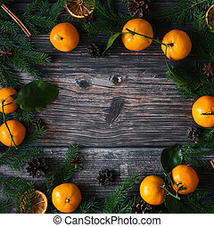 Christmas background with Mandarins, fir branches and pine cones. Winter holiday frame with cinnamon, star anise and copy space