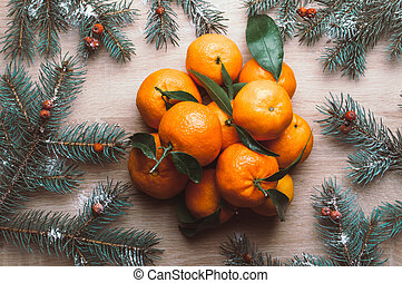 Christmas background with mandarins, fir branches and rowan berries in snow. Winter holiday frame. Flat lay top view