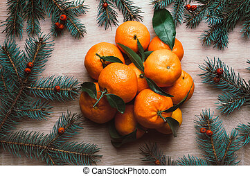 Christmas background with mandarins, fir branches and rowan berries. Winter holiday frame. Flat lay top view