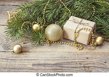 Christmas background with  pine branches, gift box and golden decorations on an old wooden table. Space for text.