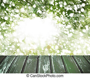 Christmas background with pine tree branch, snow and emty wooden board on abstract soft focus background