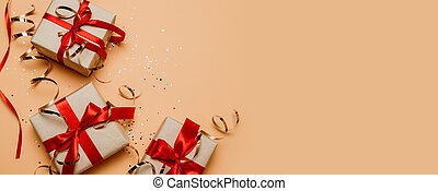 Christmas background with present box, holiday decorations on dark background. Holiday banner for website. Flat lay style composition, top view. Birthday or party greeting card with copy space