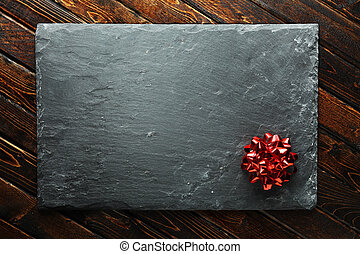 Christmas background with red bow on blank slate