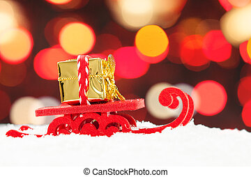 Christmas background with Santa sleigh and gold gift against abstract bokeh light background