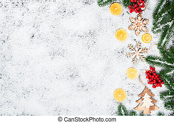Christmas background with snowflakes, white snow, toys, lemon, candy, Christmas tree branches and New Year decor. Winter Holiday Frame