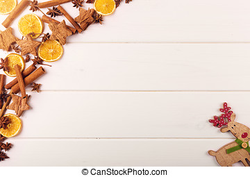 christmas background with spices and reindeer on white wooden table with copy space