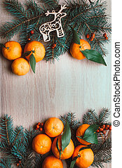 Christmas background with tangerines, fir branches and rowan berries. Winter holiday frame. Flat lay top view
