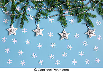 Christmas background with white snowflakes, stars, fir branches on pastel blue. Greeting card. Winter concept. Happy new year.