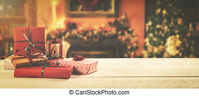 christmas background - wrapped gifts on the table in the decorated room with copy space