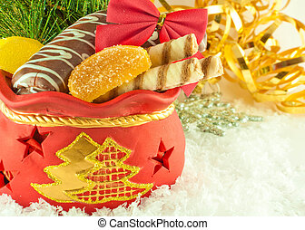 Christmas bag with gifts, cookies and fruit candy, a fur-tree branch