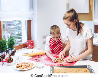 Christmas bakery. Two sisters making gingerbread, cutting cookies of gingerbread dough
