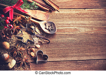 Christmas background with baking utensils, spices, anise stars, fir branches and holiday decoration on dark rustic wooden table