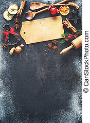 Christmas baking sweet food background with homemade cookies, spices, kitchen utensils, fir branches and red holiday decoration on dark rustic baking tray. Top view with copy space