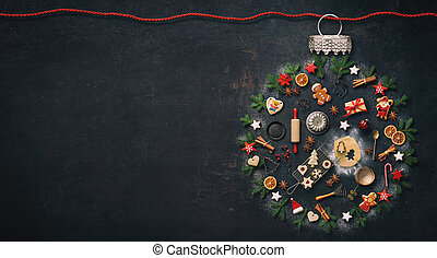 Christmas baking background with kitchen utensils cookies, spices, cinnamon sticks, anise stars laid out in the shape of a Christmas bauble on rustic baking tray, top view