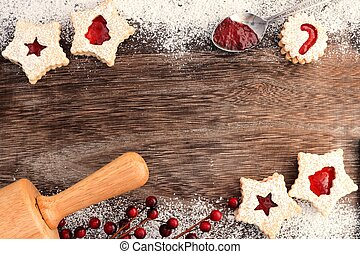 Christmas baking double border on a wooden background with Linzer jam cookies