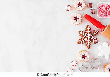 Christmas baking side border with cookies and sweets. Overhead view over a white marble background with copy space. Holiday baking concept.