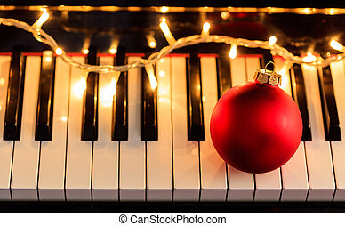 Christmas ball and lights on a piano keyboard, above view