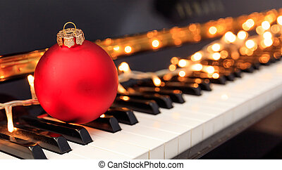 Christmas ball and lights on a piano keyboard