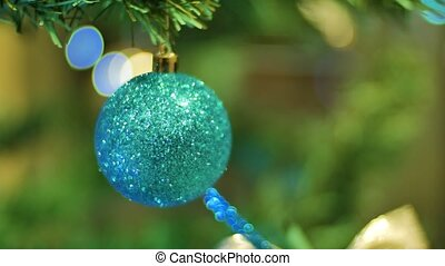 Christmas ball hanging on a branch Christmas and New Year Decoration. Blinking Garland. Christmas Tree Lights Twinkling.