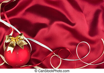 Christmas ball lying on a red fabric, can be used as background