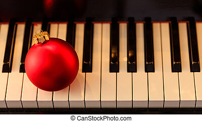 Christmas ball on a piano keyboard, above view