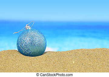 Christmas ball on sandy beach