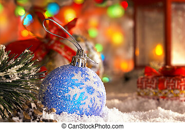 Christmas ball on snow, red lantern with a candle, garland of lights, bokeh