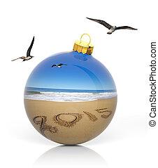 Christmas ball with 2015 written on sandy beach