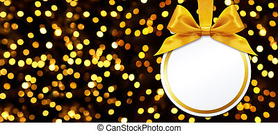 christmas ball with bow hanging on lights background
