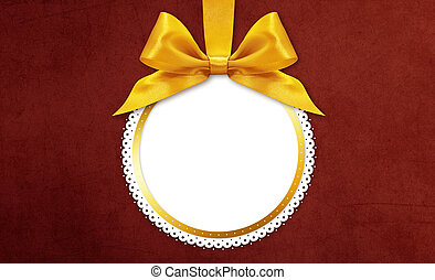 christmas ball with golden satin ribbon bow on red background