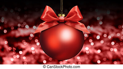 christmas ball with red satin ribbon bow on red blurred lights background