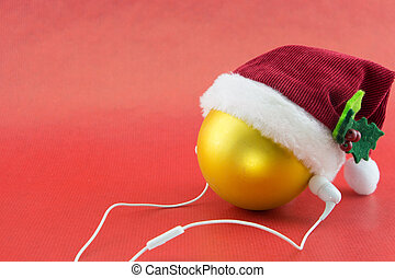 Christmas ball with Santa's hat and earphones, on red with copy-space