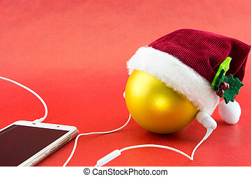 Christmas ball with Santa's hat and smartphone with earphones, on red with copy-space