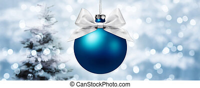 christmas ball with silver ribbon bow on blurred lights background with tree