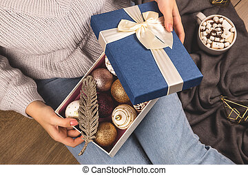 Christmas balls and decor in a box in the hands of a girl sitting on the floor.