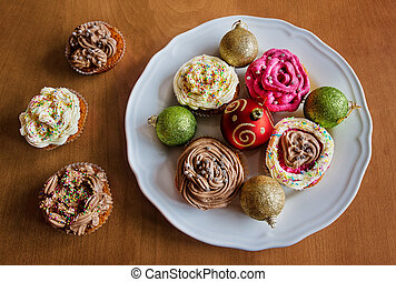 Christmas balls and  homemade cup cakes on wooden background