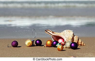 Christmas balls and seashell on the beach