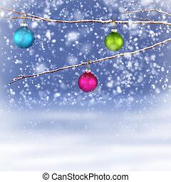Christmas balls hanging on snowy branch
