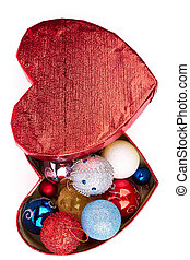 Christmas balls in heart-shaped box, top view.